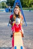 毛线衣的年轻美丽的母亲是使用和乘坐在与她的小小女儿的摇摆一个红色夹克和帽子的在 免版税库存照片