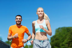 跑微笑的夫妇户外 免版税库存图片