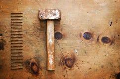 与锤子和钉子的葡萄酒木桌 免版税库存图片