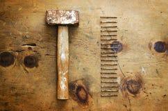 与锤子和钉子的葡萄酒木桌 库存图片
