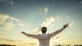 站立与他的典雅的白色衬衣的成功的人回到 免版税库存图片