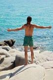 Укомплектуйте личным составом поднимать его руки или раскройте оружия стоя назад смотрящ к горизонту голубого неба моря Стоковые Изображения
