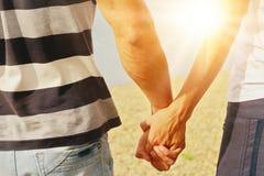 年轻人和妇女结合手拉手走在海滩 免版税库存照片