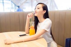 Девушка сидя в кофейне Стоковая Фотография