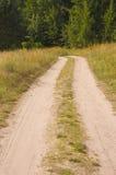农村多灰尘的乡下路的低谷领域和绿色树 免版税库存照片