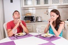 Молодые пары говоря Грейс перед едой еды Стоковое Фото