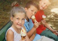 吃冰淇凌的愉快的孩子外面 免版税图库摄影