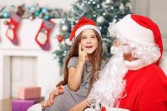 坐与圣诞老人的俏丽的女孩 库存照片