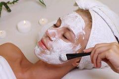 Молодая красивая девушка получая лицевую маску в салоне красоты курорта Забота кожи, косметики Стоковые Изображения RF