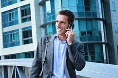 年轻英俊,成功的商人,经理谈话在电话在城市,在现代大厦前面 库存图片