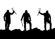 三个登山人黑剪影有冰斧的在手中 免版税图库摄影