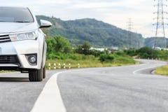 在柏油路的新的银色汽车停车处 免版税图库摄影