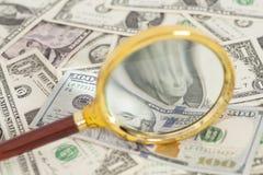 Банкноты доллара под лупой Стоковое Изображение