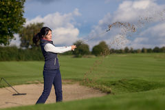 使用在沙子地堡外面的女子高尔夫球运动员 库存照片