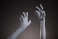 Άσπρα χέρια απόκοσμων αποκριών με τα μαύρα καρφιά που τεντώνουν επάνω Στοκ Φωτογραφίες