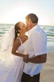 新娘&新郎亲吻的夫妇日落海滩婚礼 免版税图库摄影