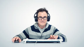 有耳机的滑稽的人在计算机前面 库存照片