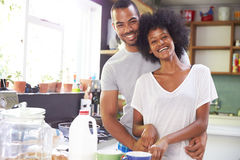一起准备早餐的年轻夫妇在厨房里 免版税库存图片