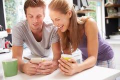 吃早餐的夫妇,检查手机 免版税库存照片