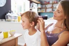母亲掠过的儿子的头发在早餐桌上 图库摄影