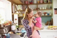 有使用膝上型计算机的年轻女儿的母亲在厨房 免版税库存照片