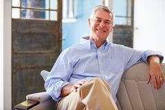 微笑的老人画象在家坐沙发 免版税库存图片