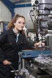Θηλυκός μηχανικός μαθητευόμενων που εργάζεται στο τρυπάνι στο εργοστάσιο Στοκ Φωτογραφίες