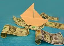 在波浪的纸小船在金钱海  免版税库存图片