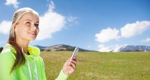 有做体育的智能手机和耳机的妇女 库存照片