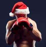 圣诞节佩带圣诞老人帽子拳击的健身拳击手 免版税库存照片