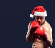 圣诞节佩带圣诞老人帽子拳击的健身拳击手 免版税库存图片