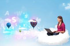 坐在与膝上型计算机的云彩的少妇 免版税库存图片