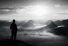 在砂岩岩石和手表的锋利的角落的单独女孩旅游宴餐秋天破晓在有薄雾的谷对太阳 免版税库存照片