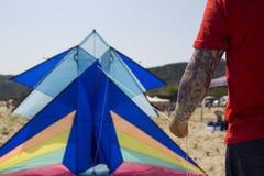 获得老的人与风筝的乐趣,举行它与一条被刺字的胳膊 免版税库存图片