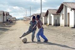踢在街道,尼加拉瓜的拉丁美州的男孩橄榄球 库存图片