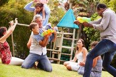 成人和孩子获得与水枪的乐趣在庭院 免版税库存照片