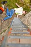 建筑工人遭受的伤害在从梯子的秋天以后 图库摄影