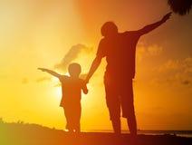 在日落海滩的父亲和儿子戏剧 免版税库存照片