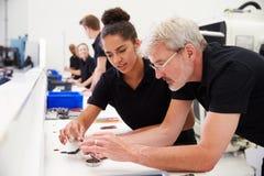 工程师在有学徒的工厂检查组分质量 免版税图库摄影