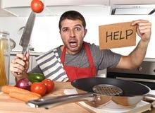 厨师围裙的年轻人在家厨房绝望在烹调重音 免版税图库摄影