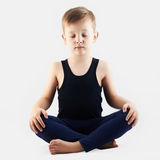 凝思儿童实践的瑜伽 小男孩做瑜伽 免版税库存照片