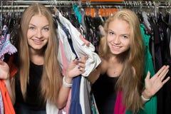 嬉戏的女朋友在服装商店 免版税库存图片