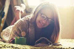 女孩阅读书用咖啡 免版税库存照片