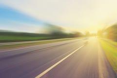 在行动迷离和阳光的空的柏油路 免版税库存照片