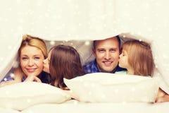 与两个孩子的愉快的家庭在毯子下在家 免版税库存照片