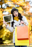 拿着购物袋和片剂在秋天的惊奇妇女 免版税库存照片