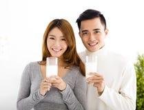 年轻微笑的夫妇饮用奶 免版税库存照片