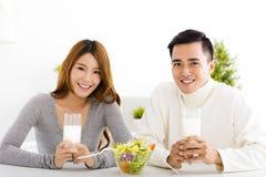 年轻微笑的夫妇饮用奶 库存图片