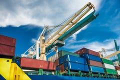 口岸起重机卸载货物与容器的货船 免版税库存图片