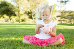 Девушка малыша кладет монетку в ее копилку снаружи Стоковые Фото